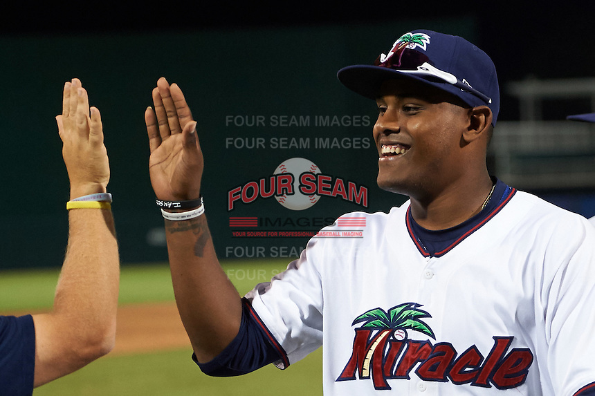 Fort Myers Miracle Brian Navarreto (23) high fives teammates after a game against the Brevard County Manatees on April 13, 2016 at Hammond Stadium in Fort Myers, Florida.  Fort Myers defeated Brevard County 3-0.  (Mike Janes/Four Seam Images)