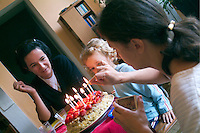 Mother, aunt and sister crowd around the table to light the candles celebrating the birthday of a nine year old boy.