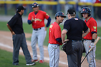 State College Spikes manager Oliver Marmol (7) argues a call with home plate umpire Dave Attridge as Michael Schulze listens in, in the background hitting coach Ramon Ortiz argues the call with base umpire Nate Caldwell, during a game against the Batavia Muckdogs on July 28, 2013 at Dwyer Stadium in Batavia, New York.  Batavia defeated State College 10-5.  (Mike Janes/Four Seam Images)