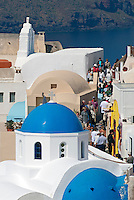 The cobblestone streets of Oia on the Greek island of Santorini bustle with shops, taverns, hotels, churches, and cafes.