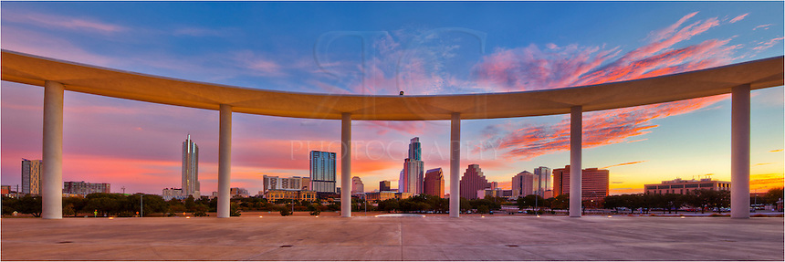 From the Long Center Pavalion, the Austin skyline and downtown Austin is peaceful at sunrise. Lady Bird Lake, while not visible, stands between these columns and and the downtown Austin area.