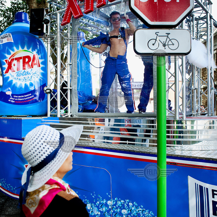 A spectator looks at a dancer on a float promoting a washing  powder. It is one of the many vehicles that form the Tour de France Caravan. This parade, consisting of cars advertising various brands and goods, travels ahead of the actual race, along the race route. According to official Tour de France website, this parade has become an essential part of the race and as many as 47% of spectators come first and foremost to see the caravan..