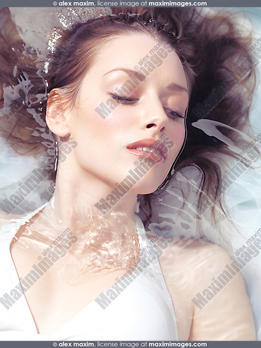 Natural look beauty portrait of a young beautiful woman lying in water in bright sunlight