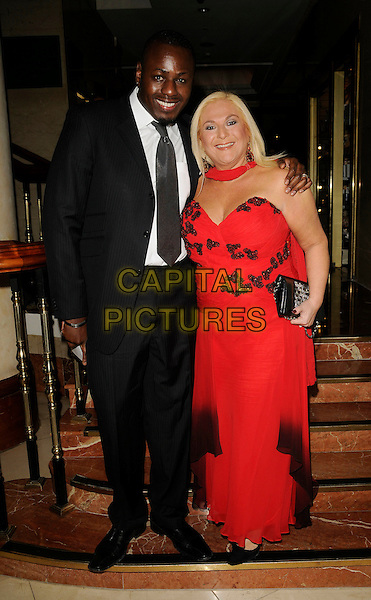 BEN OFOEDU  & VANESSA FELTZ .Inside Arrivals - The Spirit of Cuba Ball, .London Hilton Park Lane Hotel, London, England, November 15th 2008..full length black suit tie red dress strapless clutch bag fiance couple .CAP/CAN.©Can Nguyen/Capital Pictures