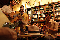 "Drink and music at Mangue Seco restaurant and cachaçaria at Lapa district in Rio de Janeiro, Brazil - musicians of the group ""Cozinha Brasileira"" playing choro and drinking cachaça. Choro, popularly called chorinho (""little cry"" or ""little lament""), is an instrumental Brazilian popular music genre which originated in 19th century Rio de Janeiro. Despite its name, the music often has a fast and happy rhythm. It is characterized by virtuosity, improvisation and subtle modulations, and is full of syncopation and counterpoint. Choro is considered the first characteristically Brazilian genre of urban popular music."