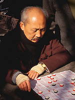 Chinese man playing board game. Shanghai, China