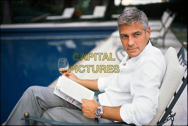 GEORGE CLOONEY.in his house in Como.Wearing Omega watch. Omega family of ambassadors..*Editorial Use Only*.half length white shirt sitting grey gray trousers reading glass wine beverage .CAP/PLF.Supplied by Capital Pictures.
