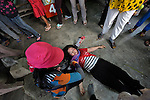A woman lies unconscious after an encounbter with police as displaced residents of Boeung Lake in Phnom Penh, who were left homeless after the government allowed a private developer to move them out and fill in the lake, attempted to protest in the Cambodian capital on December 10, 2012. They planned to take their protest to the prime minister's office, but police stopped them far short of their goal. Their protest took place on International Human Rights Day. The woman was revived and taken away in a private car.