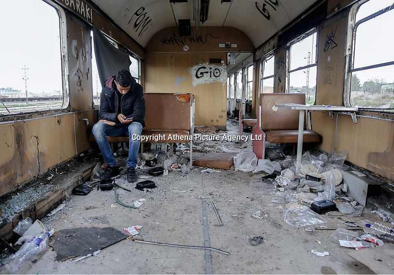 Pictured: A migrant man on his mobile phone takes shelter in a disused carriage at the OSE freight depot in Thessaloniki, Greece. Wednesday 05 April 2017<br /> Re: A year after an agreement was signed between Greece and Turkey for the management of refugees. Migrants, mostly from Morocco, Algeria and Tunisia, have been living in disused train carriages at the Thessaloniki freight depot of OSE in northern Greece, the company managing the railways in the country. Some of the migrants climb onto moving trains, or even hide themselves in storage areas, hoping that they will cross the border.