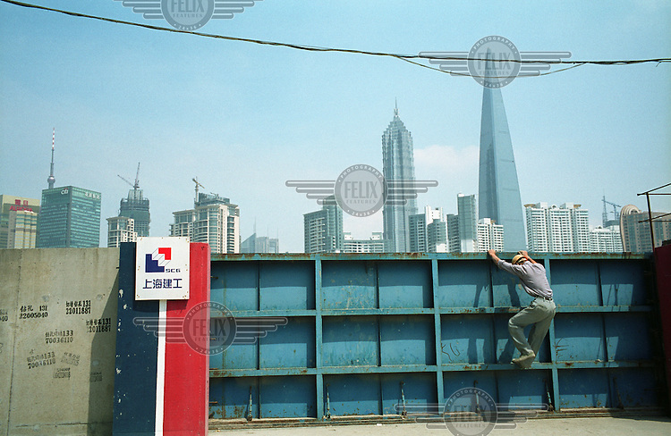 A worker climbs out of a construction site in the area collectively known as the South Bund, which is slated for redevelopment for the upcoming 2010 World Expo in Shanghai. The Pudong Financial District can be seen in the distance.