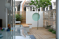 Looking out onto the tiny decked garden with moveable box benches that act as storage. Rendered wall panel provides a feature and focus to the overall design