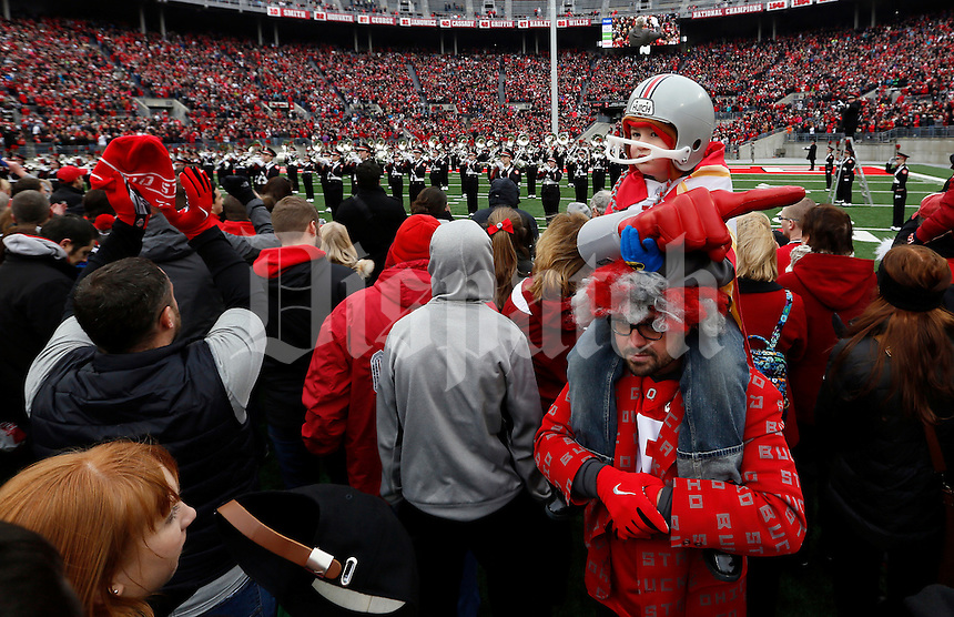 Josh Sheldon of Springborough, Ohio holds his son Hayes, 4, named after Woody Hayes, as the Ohio State Marching Band plays during the celebration for winning the national championship at Ohio Stadium on Jan. 24, 2015. (Adam Cairns / The Columbus Dispatch)