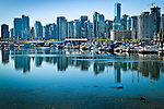 Downtown skyline from Stanley Park, Vancouver, B.C, Canada on a sunny day, early summer. Skyscrapers reflections off the  water while ducks swim by in the foreground.