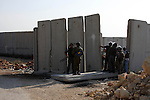 "Israeli soldiers inspect a concrete block, part of Israel's controversial separation barrier after a protest in the Qalandia refugee camp, near the West Bank city of Ramallah, on November 9, 2009 to mark the 20th anniversary of the fall of the Berlin Wall in Germany. Palestinians are using the anniversary of the end of the Berlin wall to press their campaign against Israel's ""wall"", mostly a razor-wire fence interspersed with concrete barricades which Israel began building around the West Bank in 2002. The Jewish state has come under international censure for the barrier's de facto annexation of occupied West Bank land.. Photo by Issam Rimawi"