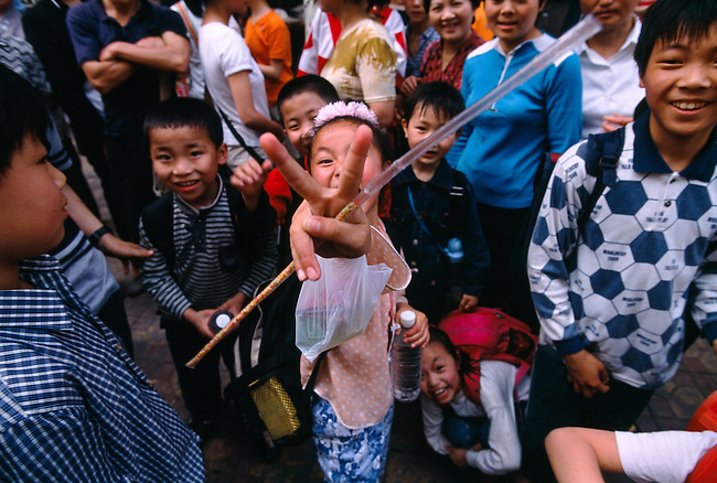 peace sign with candy straw, kids on the street react to anglo tourist with a camera, Fuling, China, Asia