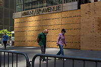 NEW YORK, NEW YORK - JUNE 08: People walk by a boarded up Armani store on June 08, 2020 in New York City. The City began first phase of reopening after nearly three months of shutdown , also Protests continue over black Americans abuse by the Police (Photo by Kena Betancur/VIEWpress via Getty Images)