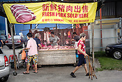 Pedestrians walk past a pork meat stall as butchers prepare cuts of meat for customers at a local wet market in Pandamaran in Klang, Selangor, Malaysia on October 16th, 2016. <br /> In September 1998, a virus among pig farmers (associated with a high mortality rate) was first reported in the state of Perak in Malaysia. Dr. Chua investigated and discovered the virus and it was later named, Nipah Virus. The outbreak in Malaysia was controlled through the culling of &gt;1 million pigs.