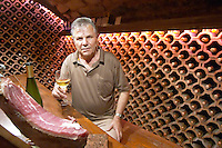 The wine cellar and tasting room where the walls are lined with bottles stacked piled in terracotta earthenware tubes.. Wine glasses on the table and a dry cured dried ham on a cutting stand. Vasilj Stanko, the owner and winemaker sitting. Vinarija Stankela Stanko winery, Medugorje, near Mostar. Medjugorje. Federation Bosne i Hercegovine. Bosnia Herzegovina, Europe.