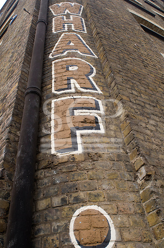 "London, England. Victorian brick warehouse wall with ""Wharf"" written on it in vertical letters and a soil pipe running down the corner."