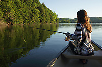 Girl with fishing rod in a canoe on a lake in Vermont as the sun rises