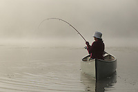 Hortonia, VT, USA - August 20, 2009: Girl in canoe catching fish on misty morning lake