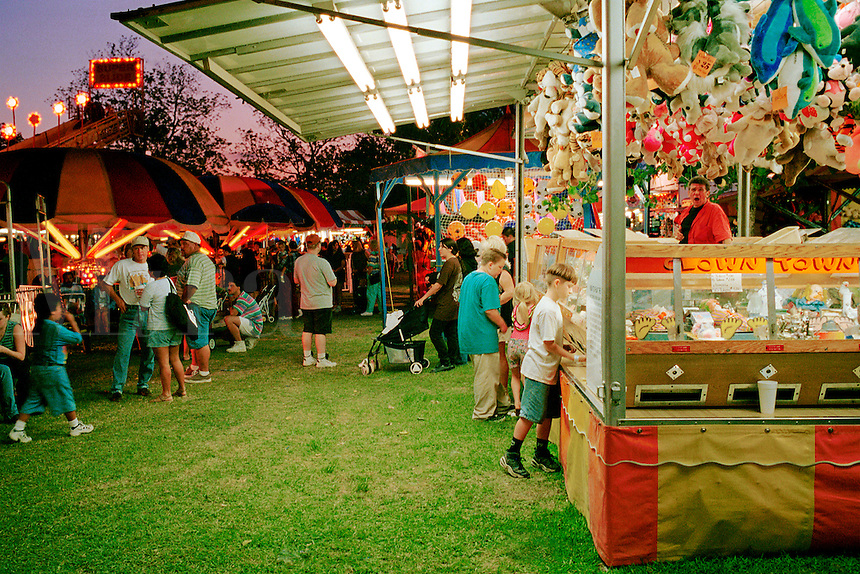 Carnival midway. Boy tries to win prize. Stuffed animal. League City Texas.