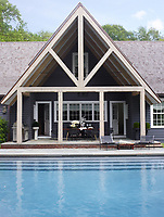 The rear facade of the house is painted in a mix of Benjamin Moore's Graphite and Gunmetal; the windows are by Marvin, and the roof is covered in cedar shingles.  The chairs by the pool provide the perfect spot to relax, whilst the pitched roof provides cover for dining al fresco on the terrace.