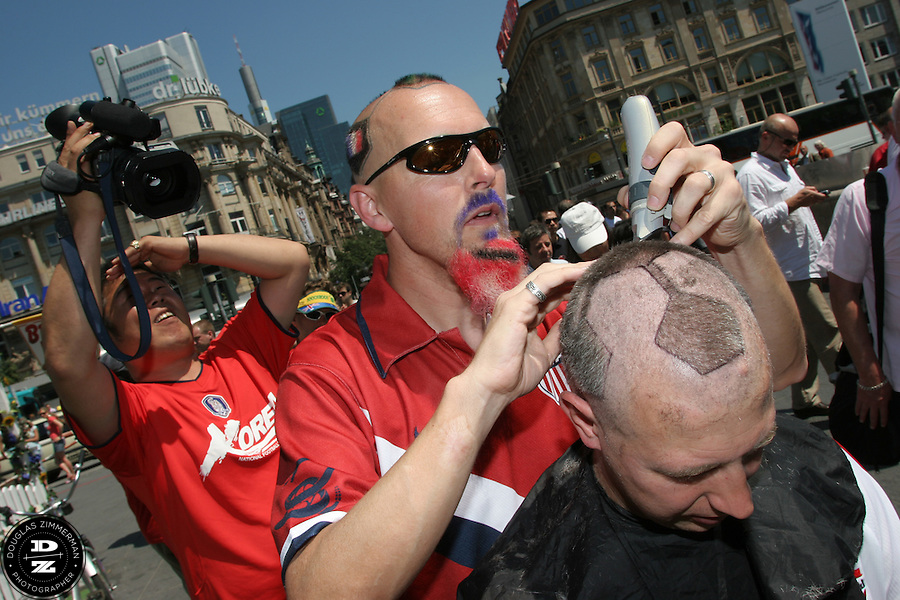 USA National Soccer Team fan Zack Phillips, also known as Mr. Soccerhead, of San Francisco, Calif. shaves the hair of Canadian soccer fan Yuri Smieska of Hamilton, Ontario  into the design of a soccer ball outside the Frankfurt Main Train Station in Frankfurt-am-Main, Germany on Tuesday, June 13, 2006.  The hair cut attracted the attention of many curious travelers. For the previous ten years, Zack Phillips has cut the hair on his head in the design of a soccerball and has even tattoed the design to make it easier to cut. At the 2002 World Cup in Korea Zack cut the hair of Yuri Smieska and Yuri asked Zack if he could do it again this World Cup. They met up outside the train station before Yuri went  to the Korea-Togo FIFA World Cup first round match in Frankfurt-am-Main with some fellow Canadian friends.
