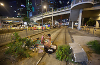 Pro-democracy protesters block the tram tracks with over-turned plant pots in Admiralty, on the second day of the mass civil disobedience campaign Occupy Hong Kong, Admiralty, Hong Kong, China, 30 September 2014. The movement is also being dubbed the 'umbrella revolution' after the versatile umbrellas used to shield protesters from rain, sun - and police pepper spray.