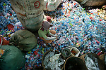 Sorting plastic see-through drinking water bottles. White caps in one bucket, colour caps into another, grey, blue and clear bottles in different containers, the wrappers to one side, everything has its place. Recycling warehouse for plastics. The plastics are sorted by recycling workers earning less than a dollar day. They throw platsic of different textures and colours into various buckets. These are collected and placed into larger sacks. The plastic is then put through a mincer (like making minced meat for hamburgers) and the small crushed picese of plastic mixed with water in the process are then dried on mats in the sun, like for coffee beans. The dry plastic shavings are bagged and shipped off for export to Thailand and Vietnam