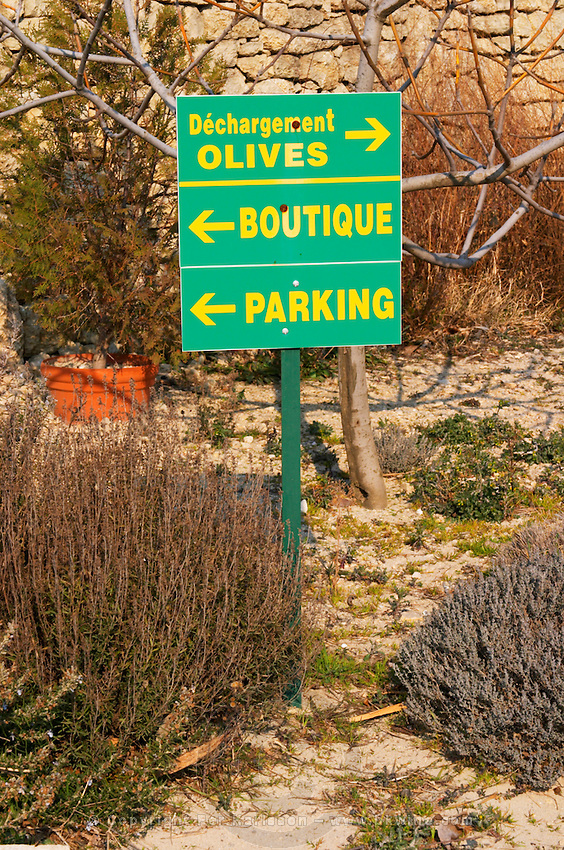 Signs showing the shop, olive delivery, parking with shrubs, rosemary romarin and thyme  at the Olive oil mill Moulin du Calanquet de Saint St Remy de Provence, Bouches du Rhone, France