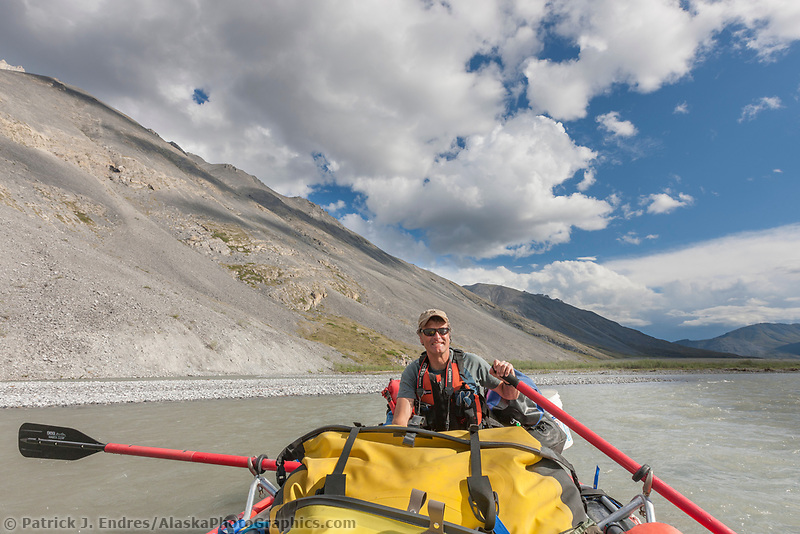 Hugh rose paddles in a raft on the Marsh Fork of the Canning River, Arctic National Wildlife Refuge, Brooks Range mountains, Alaska.