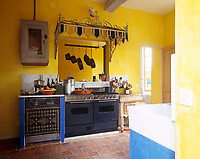 The artistic decoration of this kitchen extends to a pattern on the door of the dishwasher and an imaginative glass and wrought iron canopy above the stove