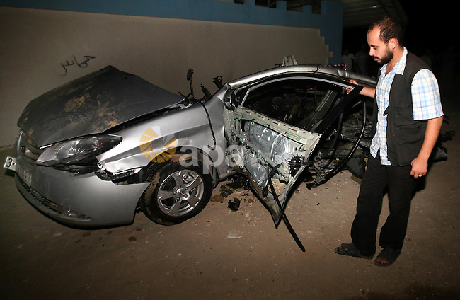 Palestinians check the damage to a car after an Israeli air strike in Rafah in the southern Gaza Strip, on August 24, 2011. Ismael Al-Asmar, one of the militant leaders of the group Islamic Jihad , was killed in the air strike by Israeli forces in the Gaza Strip. Photo by Ali Jadallah