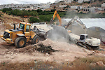 Israeli army machinery destroy a water reservoir used by Palestinian farmers in Hebron, in the Israeli-occupied West Bank, on June 14,2011.  Photo by Najeh Hahlamoun.