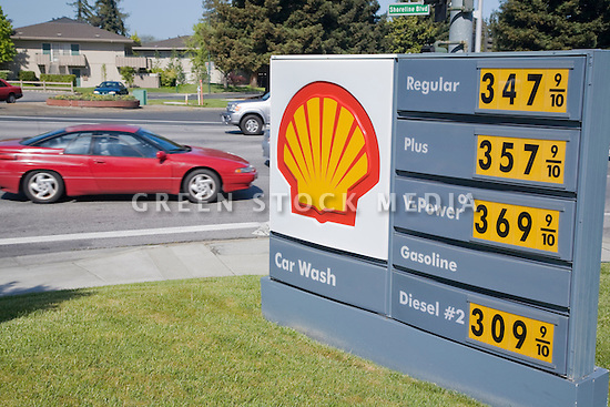 A red car passing a Shell gas price list. on April 24, 2007. Prices way over three dollars a gallon. Mountain View, California