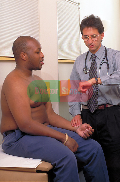 doctor checking patient's pulse