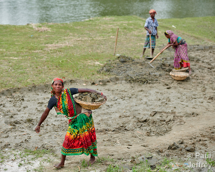 In order to raise her home a few inches, Shosida Begum (left) carries dirt in a basket in West Fasura, a village on an island in the Brahmaputra River in northern Bangladesh. Severe flooding in August 2017 destroyed the island's crops but RDRS Bangladesh, a member of the ACT Alliance, provided emergency cash grants to vulnerable island families so they could reestablish their household economies and restart their lives.