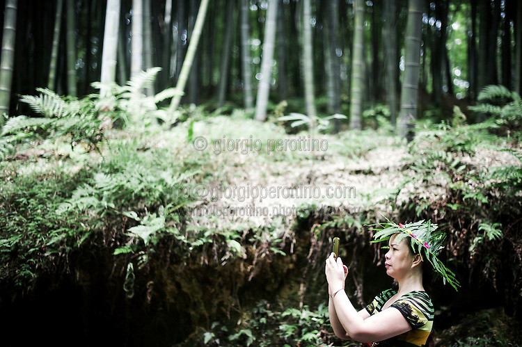 A Chinese woman takes a picture wearing a bamboo leafs' hat in the Bamboo Sea National Park in Yibin, Sichuan, China, August 07, 2014<br /> <br /> Smartphones are an essential tool of Chinese ordinary life. Everywhere in China, people use them to take pictures to share online, to talk and chat, to play videogames, to get access to the mainstream information, to get connected one each other. In the country where the main global social media are forbidden - Facebook, Twitter and Youtube are not available  -, local social networks such as WeChat have a wide spread all over the citizens. The effect is an ordinary and apparently compulsive way to get easy access to digital technology and modern way of communication. <br /> A life through the display. Yes, We Chat.<br /> <br /> © Giorgio Perottino