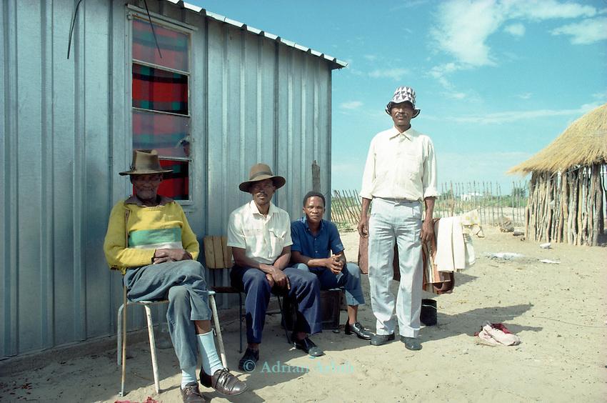 San men sitting outside  government built housing in  Tchumkwe, Bushman land, Namibia
