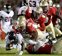 TALLAHASSEE, FL 11/19/11-FSU-UVA111911 CH-Virginia's Chase Minnifieldis sent to the turf by a Florida State's Nigel Bradham, left, Vince Williams, Beau Reliford and Timmy Jernigan during first half action Saturday at Doak Campbell Stadium in Tallahassee. .COLIN HACKLEY PHOTO