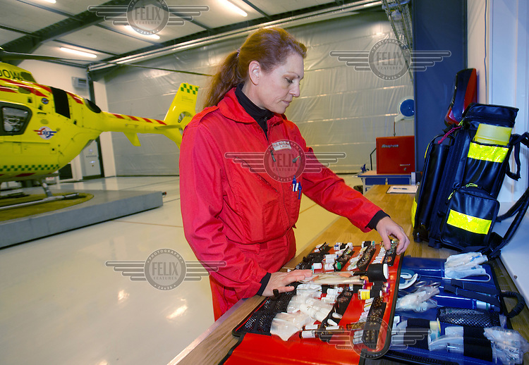 Doctor Rikke Helene Rasmussen checks the content of her medical backpack.<br /> <br /> Denmarks first  air ambulance serivce, operated by Norwegian Air Ambulance. The crew is pilot Jan Nielsen, HEMS paramedic Lars Greve-Wilms and doctor Rikke Helene Rasmussen. <br /> <br /> The crew operate an Airbus EC-135 out of the Ringsted base, one of three bases in Denmark.