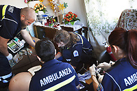 Switzerland. Canton Ticino. Lugano. Paramedics team at work. A senior man is lying down unconscious due to a heart attack. Myocardial infarction (MI), commonly known as a heart attack, occurs when blood flow decreases or stops to a part of the heart, causing damage to the heart muscle. 45 minutes after arrival, with no restart of heart beats, the emergency doctor had to declared the man dead. Paramedics team wears blue uniforms and work for the Croce Verde Lugano. The man (C) and the woman (C) are professional certified nurses, the other bald man (L) and the woman (R) the other man (L) are volunteers specifically trained in emergency rescue. On the couch, a monitor is used to controls vital functions, such as electrocardiogram, blood pressure's measurement, respiratory rate and pulse oximetry (oxygen saturation).The Croce Verde Lugano is a private organization which ensure health safety by addressing different emergencies services and rescue services. Volunteering is generally considered an altruistic activity where an individual provides services for no financial or social gain to benefit another person, group or organization. Volunteering is also renowned for skill development and is often intended to promote goodness or to improve human quality of life. 13.01.2018 © 2018 Didier Ruef