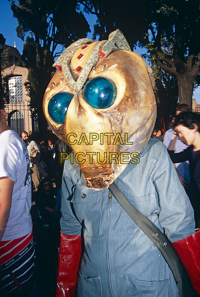 Demonstrator dressed as an insect wearing unusual headwear, Rome, Italy