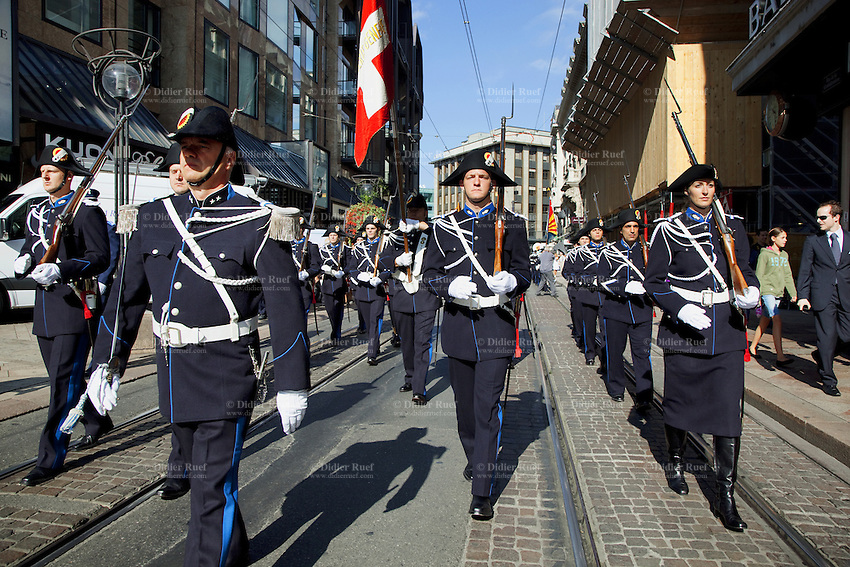 Switzerland. Geneva. A group of recruits ( policemen and policewomen) from the police academy march on the day in which they will be all sworn in as police officers. They wear uniforms, white gloves, tricorns on the heads and carry old rifles with bayonet on the shoulders. The tricorne or tricorn is a style of hat that was popular during the 18th century, falling out of style by 1800. The tricorne was worn as part of military uniforms. A bayonet (from French ba«onnette) is a knife, sword, or spike-shaped weapon designed to fit in, on, over or underneath the muzzle of a rifle, effectively turning the gun into a spear. The flag of Switzerland consists of a red flag with a white cross (a bold, equilateral cross) in the centre. It is a sovereign-state flag. 29.08.12 © 2012 Didier Ruef...