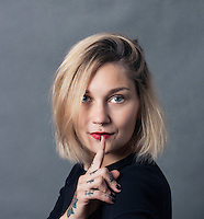 Blond women with tatoos on her hand and arm, holding her finger up to her closed mouth. Woman wearing black blouse. Photographed on grey backdrop.