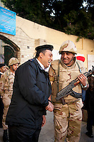 Egypt / Cairo / 22.12.2012 / A soldier and a policeman laugh together out of a polling center in Agouza's neighbourhood. Egyptians cast their ballots during the second day of the constitutional referendum, on December 22nd. © Giulia Marchi