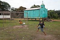 Amazonian children play soccer in a riverside village near Manaus, beside Negro river, Amazon rain forest, Brazil.