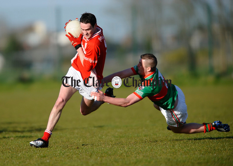 Eire Og's Donie Lyne is tackled by Enda Coughlan of Kilmurry Ibrickane during their Cusack Cup game in Ennis. Photograph by John Kelly.