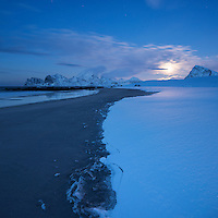 Moon rises over snow covered Storsandnes beach in winter, Flakstadøy, Lofoten Islands, Norway